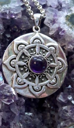Round amethyst pendant with ornate sterling silver setting